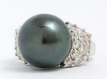 Lady's 14K White Gold Dinner Ring, with a 15mm round greenish black South Seas pearl, flanked by three stepped graduated bands of ro..