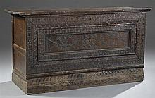 Continental Carved Walnut Blanket Chest, early 19th c., with an incised floral and figural front panel, on a pierced plinth base, H....