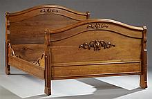 American Classical Carved Walnut Double Sleigh Bed, 19th c., the arched headboard with applied relief decoration, the footboard with...