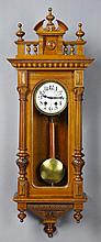 German Carved Walnut Wall Clock, c. 1900, time and strike, the broken arch crest with turned finials, over a spindled gallery above...