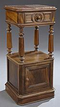 French Louis Philippe Carved Walnut Marble Top Nightstand, 19th c., the inset canted corner highly figured rouge marble over a friez...