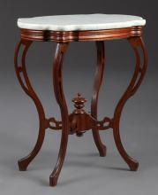 American Victorian Carved Mahogany Marble Top Lamp Table, late 19th c., the highly figured white turtle marble over a carved skirt,...