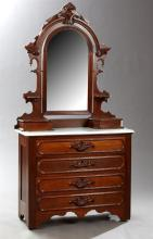 American Victorian Carved Walnut Marble Top Dresser, late 19th c., the arched mirror flanked by two candle stands above two lift top...