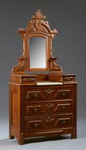 American Renaissance Revival Carved Mahogany Dropwell Dresser, late 19th c., the arched crest mirror flanked by two candle shelves,...