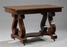 American Classical Revival Carved Mahogany Library Table, early 20th c., the rectangular top over a wide skirt with a frieze drawer...