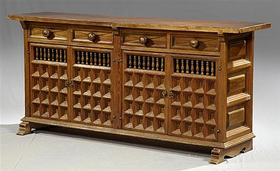 Italian Carved Walnut and Oak Renaissance Style Sideboard, late 19th c., with four frieze drawers over double cupboards with spindle...