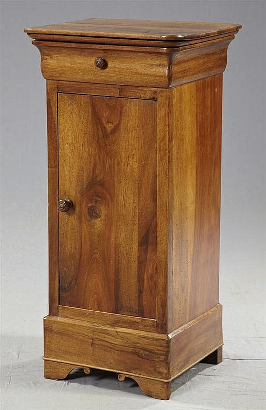 Louis Philippe Carved Walnut Night Stand, c. 1850, the rounded corner top over a sloping front frieze drawer above a tall cupboard d...