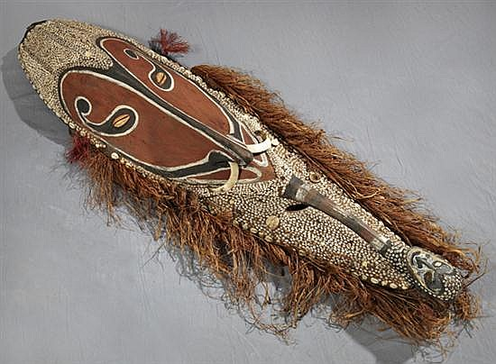 Large New Guinea Carved Wooden Mask, 20th c., mounted with cowrie shells, boars tusks, and raffia hair, H.- 54 1/2 in., W.- 13 1/2 i...