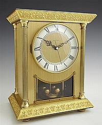 Brass Anniversary Style Mantel Clock, 20th c., by Hettich, the stepped relief edge sloping top over columnar sides, and a window for...