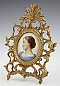German Hand Painted Porcelain Plaque, c. 1880, of a woman in a blue dress, presented in a pierced gilt spelter tabletop easel frame,...