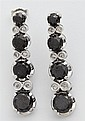 Pair of 14K White Gold Pendant Earring, each with flour graduated round black diamonds joined by three links mounted with two round...