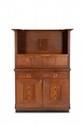Arts and Crafts  Meuble à deux corps en chêne à partie basse  avancée ouvrant à deux portes et deux tiroirs  et partie haute à niches et étagère dominée  par un fronton débordant.  H. : 180 cm. L. : 124 cm. P. : 54 cm.
