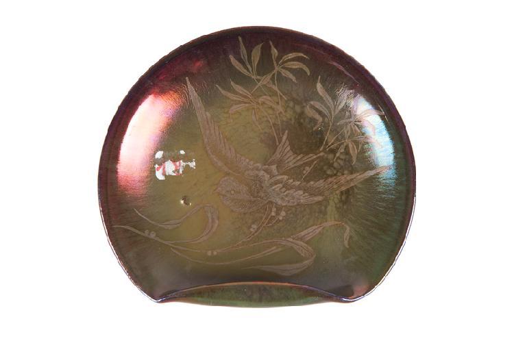Jean-Baptiste Gaziello  (1871-1957)  Assiette ronde à bord retourné en céramique  irisée à décor d'oiseau. Signée. D. : 17,5 cm.