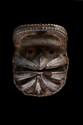 Masque Guerrier We-Guéré ou Glé-Bété, Côte d'Ivoire. Bois à patine brun-noir, clous de laiton. H : 30 cm. Restauration aux cornes et petits manques. Masque à forte puissance expressive sur lequel se rabattent sept cornes sculptées garnies de clous