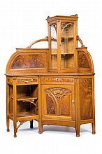 Léon Bénouville (1860-1903) attribué à Meuble d'angle en bois fruitier et acajou flammé à vitrine centrale en angle en partie haute et ouvrant en partie basse par une porte en biais avec une étagère ouverte à gauche. Sculpture naturaliste sur la