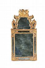 Glace de salon en bois doré dans un cadre à réserves avec palmettes et rinceaux en écoinçons. Fronton sculpté d'attributs guerriers (casques, étendards et carquois entre des rinceaux feuillagés).   Epoque Régence.   H. : 1,66 m. L. : 84 cm.