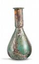 GRAND FLACON EN VERRE  A panse piriforme et col tubulaire étranglé à la base. Concrétions et irisations.  Intact. Epoque romaine. H. : 18 cm.