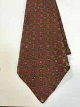 HERMES PARIS  Cravate en soie imprimée. Fond bordeaux à décor de