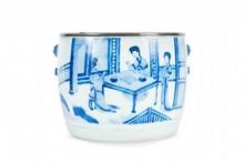 Jardinière en porcelaine bleu blanc Chine, Dynastie Qing, époque Kangxi (1662-1722). De forme circulaire, décorée de deux grands cartouches de scènes animées, l'un de femmes dans un intérieur, l'autre de dignitaires et serviteurs, quatre masques et