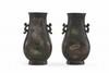 Paire de vases en bronze  Chine, XIXème siècle.  De forme balustre quadrangulaire reposant sur un  petit pied droit, à décor de motifs archaïsants, un félin  de chaque côté du col formant les anses, inscription à  la base ; oxydation. H. : 19 cm.