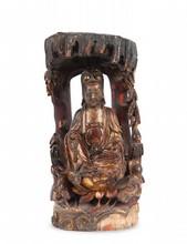 Statue de Guanyin en bois sculpté et laqué rouge et or Chine du sud, XVII-XVIIIème siècle. Représentée assise sur un lotus émergeant de flots, sous un dais rocheux, un châle recouvrant sa coiffe et tombant sur les épaules, la main droite reposant sur