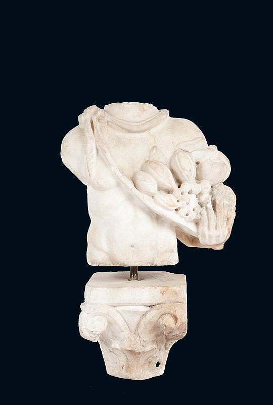 Torse de VertumnusDieu nu, les épaules en partie couvertes d'une dépouille animale, il porte de la main gauche un régime de fruits.Il repose sur le chapeau d'une colonne.Marbre blanc.Art Romain, IIème siècle après J-C.H. : 35 cm.