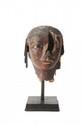 GRANDE TÊTE ÉGYPTIENNE EN BOIS Sculpté et polychromé. Perruque noire striée ; visage brun ; sourcils, contour des yeux et pupilles noirs ; yeux gravés en léger creux. (Restaurations). Tête appartenant à une statue grandeur nature. Egypte. Ancien