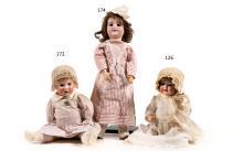 Bébé allemand à tête caractérisée bouche ouverte marquée SIMON & HALBIG 126, yeux riboulants bleus, corps en composition semi-droit. H. : 48 cm. (A signaler un éclat à l?oeil).