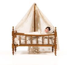 Bébé allemand à tête caractérisée bouche ouverte marquée SIMON &HALBIG 126, yeux dormeurs bleus, corps d?origine à membres torses. Epoque 1900. H. : 39 cm. Présentée dans un lit en bois naturel.