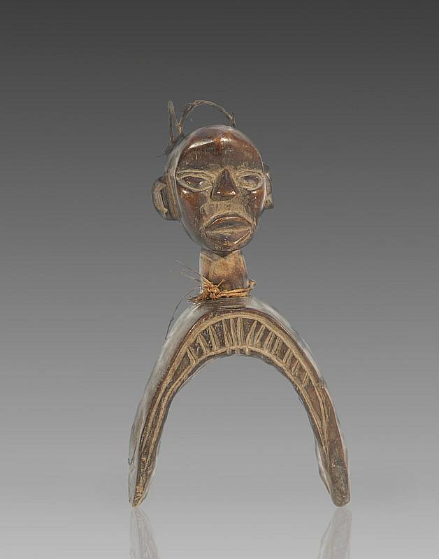Etrier de poulie de métier à tisser DAN, Côte d'Ivoire. Large étrier surmonté d'une tête aux traits cubisants. Bois à patine brun roux. H.: 21 cm.