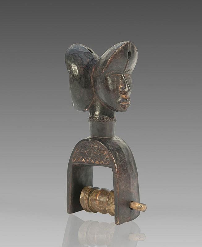 Etrier de poulie de métier à tisser DAN, Côte d'Ivoire. Surmonté d'un tête janiforme. Bois à patine brun noir. H.: 19 cm.
