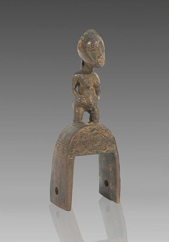 Etrier de poulie de métier à tisser BAOULÉ, Côte d'Ivoire. Belle représentation de l'épouse de l'au-delà debout sur l'arceau. Bois à patine brun roux. H.: 18 cm.