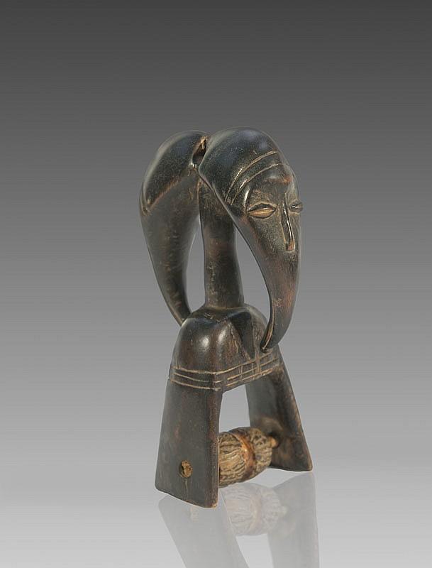 Etrier de poulie de métier à tisser DAN, Côte d'Ivoire. Large étrier surmonté d'une tête janus figurant un masque de type Maou. Bois à patine brun noir. H.: 18 cm.