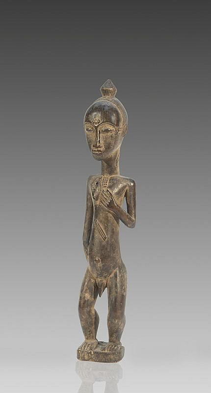 Statuette Blolo Bian BAOULÉ, Côte d'Ivoire. Personnage masculin debout représentant l'époux de l'au-delà. Regard doux et serein. Bois à patine noire brillante par endroits. Erosions dans le dos. H. : 43 cm. Collecté in situ par son actuel