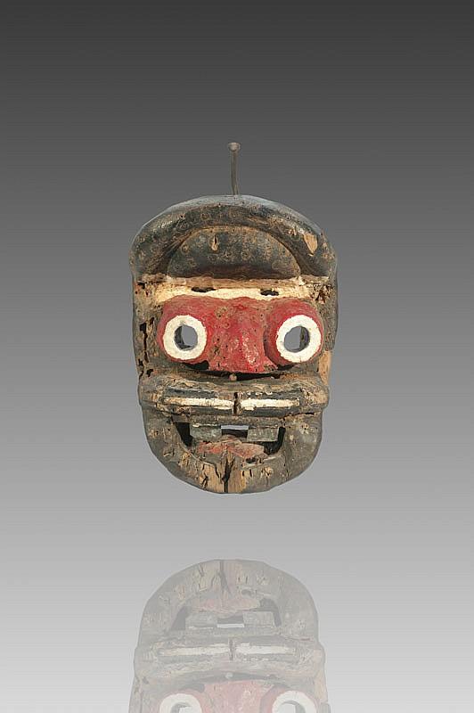 Masque de danseur BETE-WOBE, Côte d'ivoire. La bouche entrouverte laissant apparaître deux dents en fer, le nez large, les yeux tubulaires, le front bombé. Bois érodé, métal et pigments de couleur. H. : 26 cm. Collecté dans le canton de Bangolo