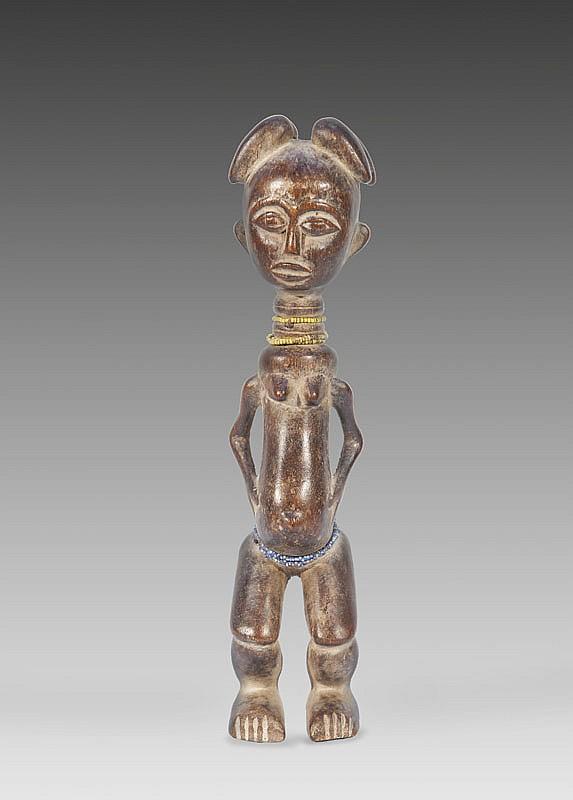 Statuette de fécondité  AGNI, Côte d'Ivoire.  Personnage féminin debout les jambes  légèrement fléchies, les mains posées de  part et d'autre de son abdomen proéminent.  Bois à patine miel.  H. : 31 cm.