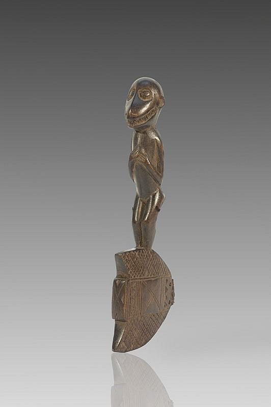 Marteau de gong BAOULÉ, Côte d'Ivoire. Surmonté d'une statuette zoomorphe représentant un singe mendiant dit «Bécré», positionné dans une attitude classique de récipiendaire d'offrandes. Bois à patine brun clair. H.: 25 cm.