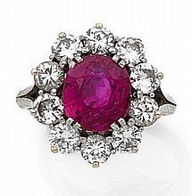 Bague en or gris sertie d'un rubis de forme coussin dans un entourage de 10 diamants taillés en brillant.