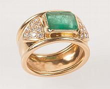Bague en or jaune sertie d'une émeraude rectangulaire épaulée de deux pavages de diamants taillés en brillant.