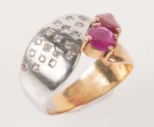 Bague en or jaune et or gris sertie de deux rubis, l'un ovale, l'autre navette et petits diamants taillés en brillant.