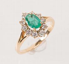Bague en or gris sertie d'une émeraude rectangulaire dans un entourage de petits diamants taillés en brillant.