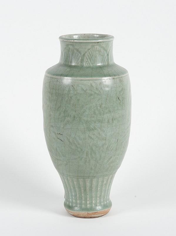 Vase en grès émaillé céladon  Chine, époque Ming, Longquan, XVème siècle.  De forme balustre, à décor moulé de fleurs, palmes et cannelures.  Craquelures. H. : 26,5 cm.
