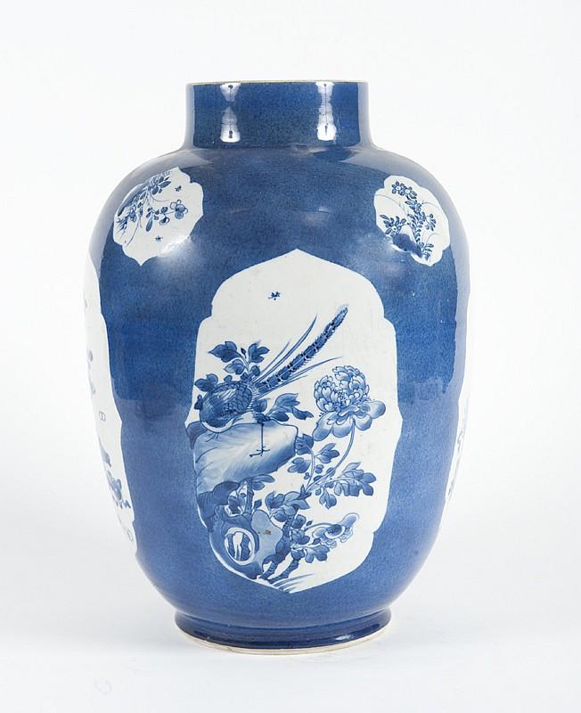 Vase en porcelaine bleu-blanc et bleu poudré  Chine, XVIIIème - XIXème siècle.  De forme ovoïde, décoré de cartouches d'objets  mobiliers, faisans et pivoines, sur fond bleu poudré.  Fêle au col. H. : 36 cm.