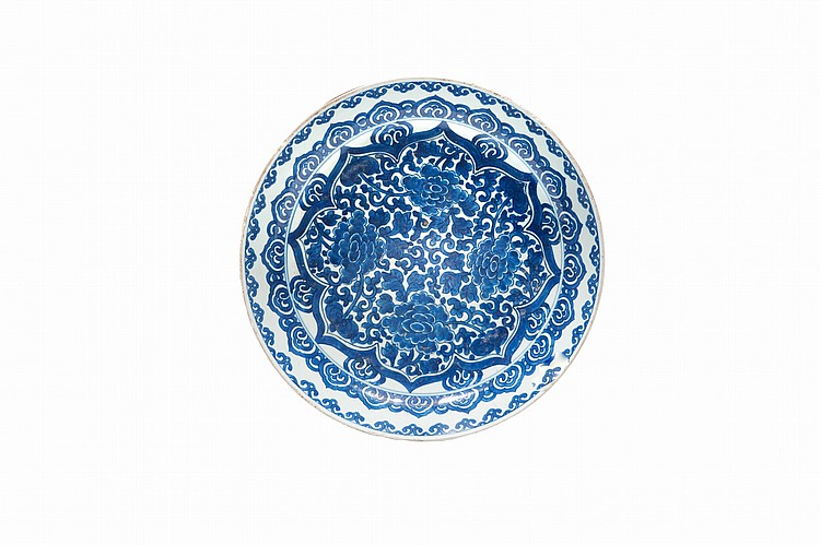 Plat en porcelaine bleu-blanc  Chine, époque transition, XVIIème siècle.  Le centre décoré de pivoines dans un médaillon lobé, l'aile  de frises de Ruyi. Fêle.  D. : 34 cm.