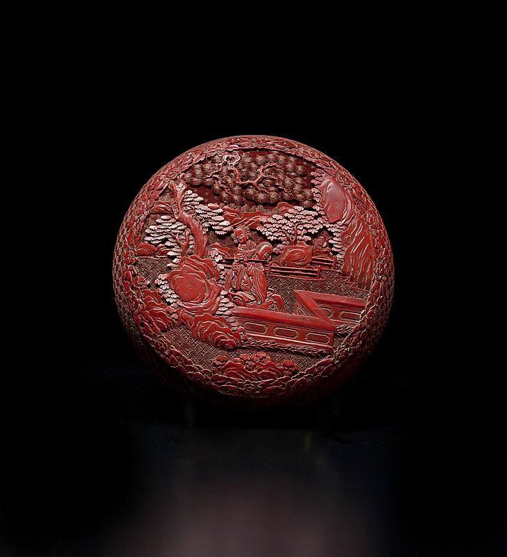 Boîte circulaire couverte en laque sculptée Chine, époque Jiaqing (1796-1820). Le couvercle orné d'un médaillon central décoré de deux musiciennes sur une terrasse entourée de rochers, pin et arbustes, frise de pivoines, le pourtour sculpté de motifs
