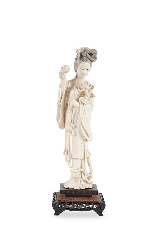Statuette de femme en ivoire sculpté  Chine, première moitié du XXème siècle.  Représentée debout, tenant une pivoine dans sa main droite, socle en bois.  H. : 25 cm.