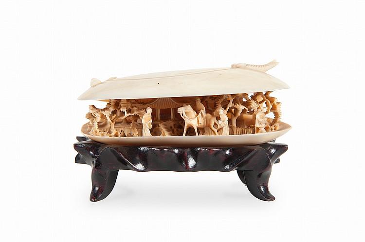 Palourde en ivoire sculpté.  Chine, première moitié du XXe siècle.  La palourde entrouverte et laissant entrevoir une scène de cavalier, arbres et  pagode. Le dessus sculpté d'un coquillage et d'un poisson. 4,5 x 10 cm.