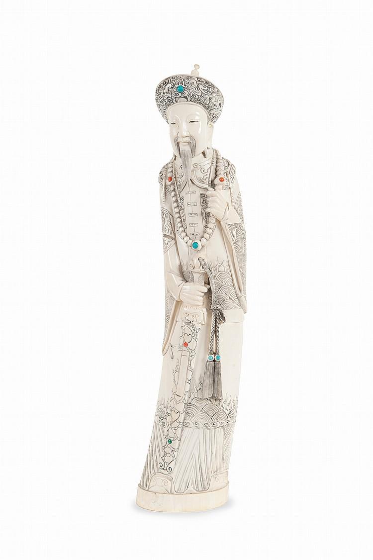 Deux groupes en ivoire sculpté Chine. Travaillés dans la courbure de la défense, représentant l'un un officiel tenant un glaive, l'autre une dame de cour tenant un sceptre ruyi. Incrustations de pierres dures. Extrémité du chapeau du dignitaire