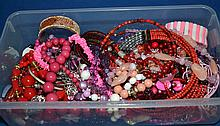 BOX OF PINK AND RED TONE COSTUME JEWELRY  All jewelry sold as is.