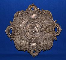 ROCOCO REVIVAL METAL CHARGER   Rococo revival silvered metal charger.  Center medallion of putti pierced scrolling border.  Hander on back.  15'' diam. No Mark.  Condition age appropriate wear.  Some wear to metal finish.